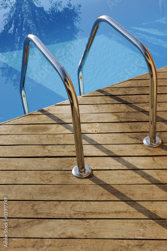 Swimming pool handrail with teak wood flooring