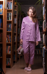 Girl in pajamas and slippers at night in the library