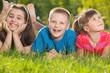 Three happy kids on the grass