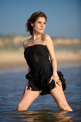 Mulher com vestido preto na praia dentro de àgua