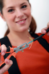 female electrician using wire cutter
