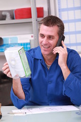 Man checking product details by phone in a plumber's merchants