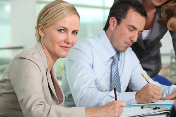 Businesswoman holding pen sat next to colleague