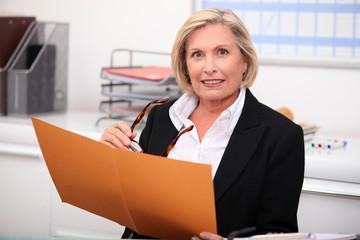 Mature businesswoman holding an open file