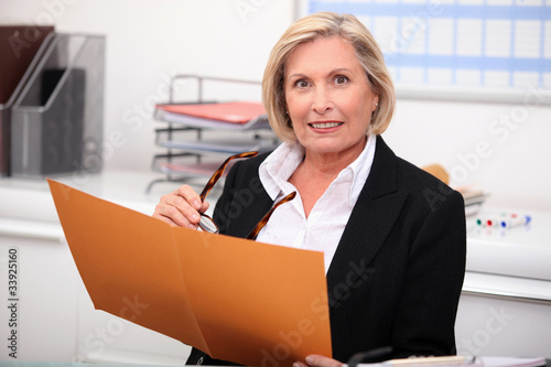 Mature businesswoman holding an open file