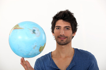 Man spinning a globe on his fingertips