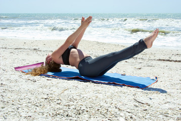woman doing yoga exercise on beach in full expression of fish po