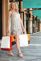 Woman with shopping bags outside boutiques
