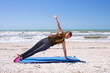 young woman doing yoga exercise on beach in Vasisthasana or side