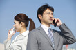 携帯電話で通話するOLとビジネスマン