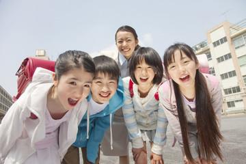 笑顔の小学生4人と女性教師