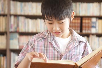 図書室で本を読む小学生男子