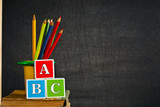 Fototapety ABC and multicolored pencil on old textbook against blackboard