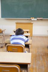 退屈そうに机に寝そべる小学生男子の後ろ姿
