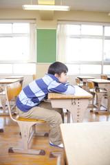 退屈そうに机に寝そべる小学生男子