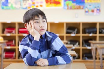 教室の机で退屈そうにしている小学生男子