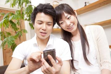 スマートフォンを操作するカップル