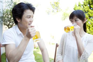 庭でビールを飲むカップル