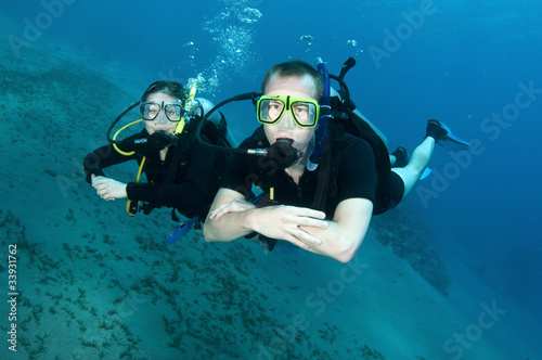 Scuba divers swim underwater in clear blue water