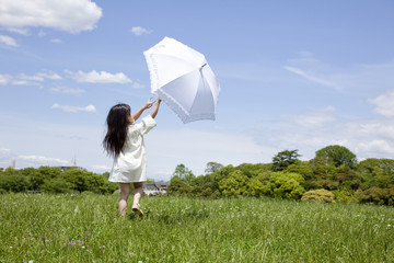 日傘を差して草原を歩く女の子の後ろ姿