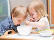 Funny children are eating dessert