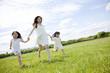 草原を走る女の子2人と若い女性