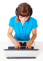 Red-haired teen-girl listen to music in headphones with laptop