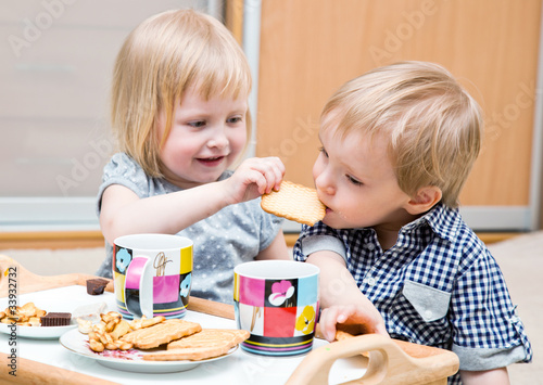 Funny children are eating dessert