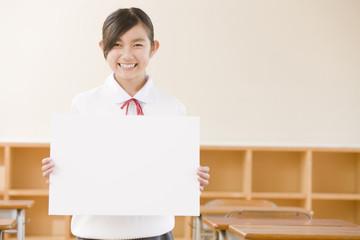 教室でメッセージボードを持つ女子中学生