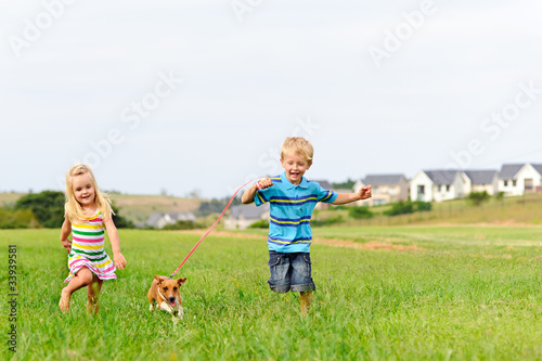 Cute blond kids running in a field