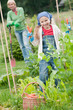 Gardening -  girl helping mother in the vegetable garden