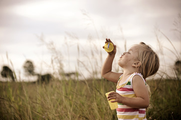 Carefree girl playing in the field, blowing bubbles