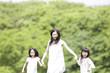 手を繋いで走る大人の女性と2人の子供