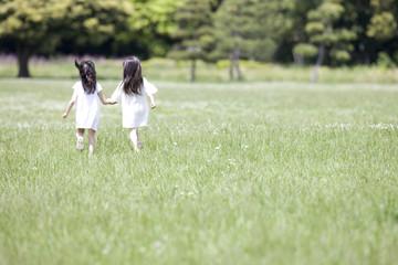 手を繋いで走る2人の女の子の後姿