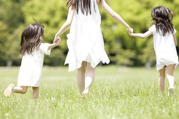 手を繋いで走る大人の女性と2人の子供の後姿