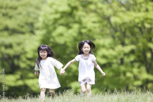 手を繋いで走る2人の女の子