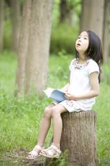 切り株に座り本を読む女の子