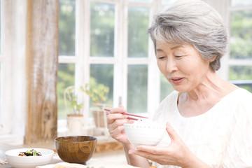 朝御飯を食べるシニア女性