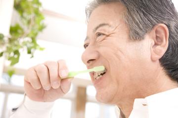 歯を磨くシニア男性