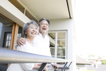 ベランダで笑っている老夫婦