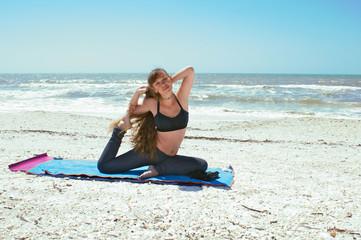 woman doing yoga exercise on beach in Kapotasana or Pigeon Pose