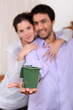 Couple holding miniature bin