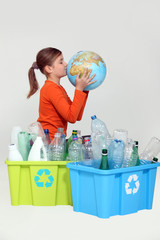 Young girl kissing the planet next to her recycling
