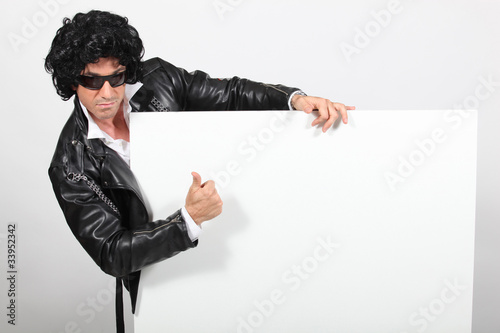 Man dressed as Elvis holding message board