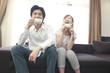 ソファでコーヒーを飲みながら談笑するカップル