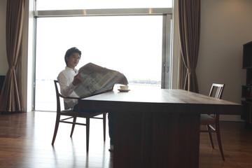 ダイニングテーブルで新聞を読む男性