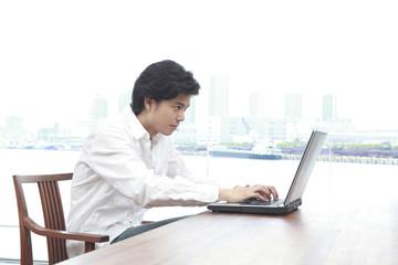 ダイニングテーブルでノートパソコンを使う男性