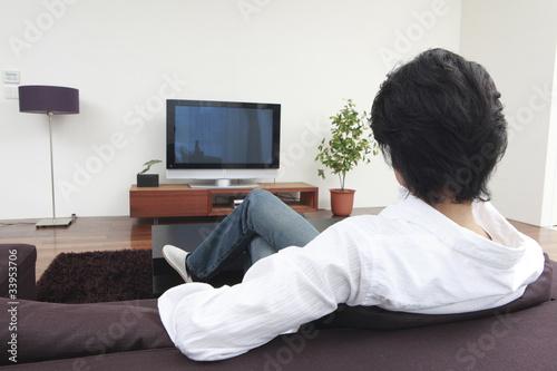リビングでテレビを見る男性の後姿