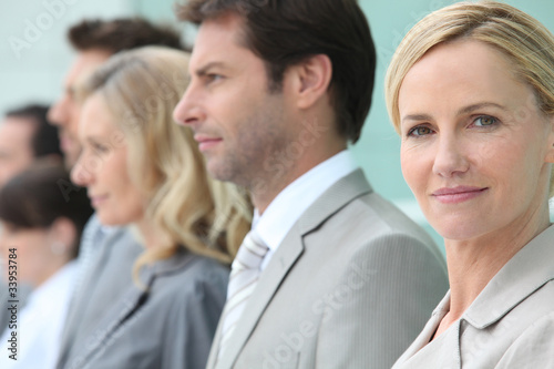 Businesswoman standing in a line with colleagues
