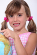 Young schoolgirl pointing to a destination on a globe